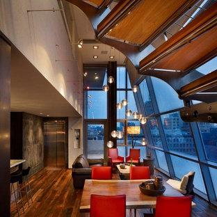 Idee per una piccola sala da pranzo aperta verso il soggiorno industriale con pareti beige, parquet scuro, nessun camino e pavimento marrone
