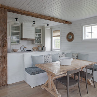 Example of a mid-sized coastal light wood floor and brown floor kitchen/dining room combo design with white walls