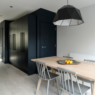 Small contemporary open plan dining room in Sussex with white walls, light hardwood flooring and white floors.