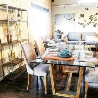 Foto di una sala da pranzo aperta verso il soggiorno contemporanea di medie dimensioni con pavimento in laminato, pareti gialle e pavimento marrone