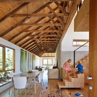 Idées déco pour une salle à manger ouverte sur la cuisine campagne avec un mur blanc et un sol en bois brun.