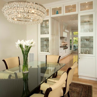 Example of a large classic light wood floor and beige floor enclosed dining room design in DC Metro with white walls