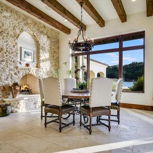 Ispirazione per una sala da pranzo mediterranea con pareti bianche, camino classico, cornice del camino in pietra e pavimento beige