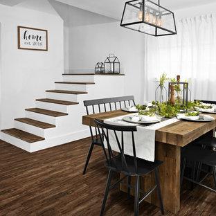 Idées déco pour une salle à manger ouverte sur le salon campagne de taille moyenne avec un mur blanc, un sol en vinyl, aucune cheminée et un sol marron.