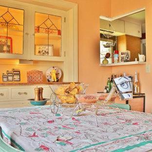 Immagine di una sala da pranzo boho chic chiusa con pareti arancioni