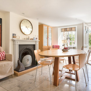Example of a mid-sized country ceramic tile dining room design in Devon with white walls and a standard fireplace