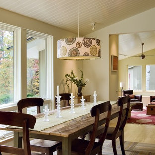 Example of a trendy medium tone wood floor dining room design in Burlington with beige walls