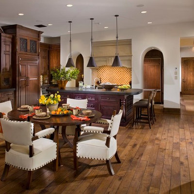 Example of a tuscan dark wood floor kitchen/dining room combo design in Orange County with white walls