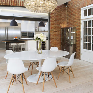 Idee per una sala da pranzo aperta verso la cucina minimal con parquet chiaro, pareti rosse e nessun camino