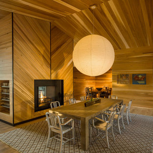 Ispirazione per un'ampia sala da pranzo aperta verso il soggiorno stile rurale con pareti marroni, pavimento in legno massello medio, camino classico, pavimento marrone e cornice del camino in metallo