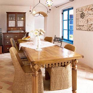 Réalisation d'une petite salle à manger ouverte sur la cuisine méditerranéenne avec un mur blanc, un sol en brique et un manteau de cheminée en bois.