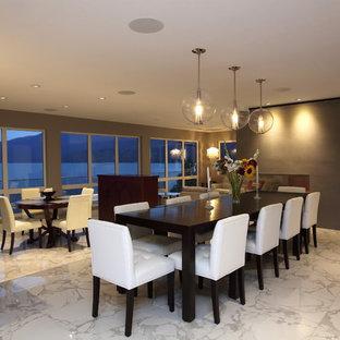 Modelo de comedor minimalista, grande, abierto, con paredes grises, suelo de mármol, chimenea de doble cara y marco de chimenea de yeso