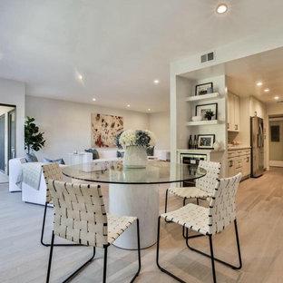 Idées déco pour une salle à manger ouverte sur la cuisine moderne de taille moyenne avec un mur gris, sol en stratifié, aucune cheminée et un sol marron.