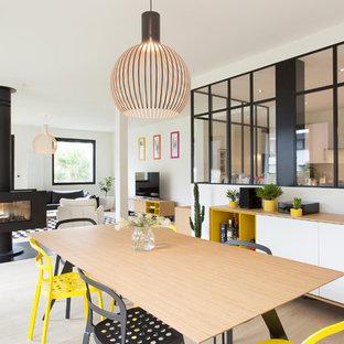 Mittelgroßes, Offenes Modernes Esszimmer mit weißer Wandfarbe, hellem Holzboden, Tunnelkamin und Kaminumrandung aus Metall in Rennes