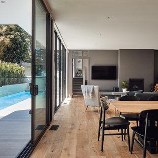 Foto di una sala da pranzo aperta verso il soggiorno contemporanea di medie dimensioni con pareti grigie, parquet chiaro, camino classico, cornice del camino in cemento e pavimento marrone
