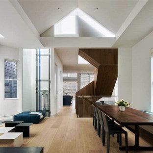 На фото: большая гостиная-столовая в стиле модернизм с белыми стенами, светлым паркетным полом, угловым камином и фасадом камина из плитки с