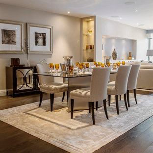 Classic open plan dining room in London with beige walls and dark hardwood flooring.
