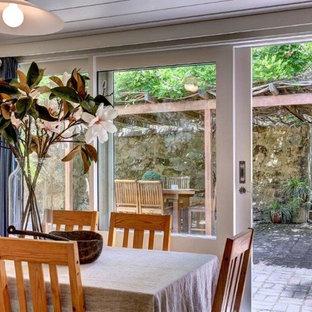 アデレードの中くらいのカントリー風おしゃれなダイニングキッチン (黄色い壁、コルクフローリング、ベージュの床) の写真