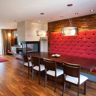 Esempio di una sala da pranzo aperta verso il soggiorno design con pareti beige, pavimento in legno massello medio, camino bifacciale e cornice del camino in pietra