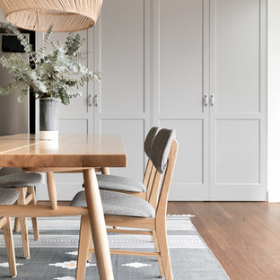 Mid-sized transitional open plan dining in Sydney with white walls, medium hardwood floors, brown floor and a wood fireplace surround.