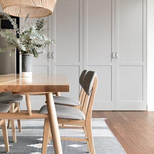 Modelo de comedor tradicional renovado, de tamaño medio, abierto, con paredes blancas, suelo de madera en tonos medios, suelo marrón y marco de chimenea de madera