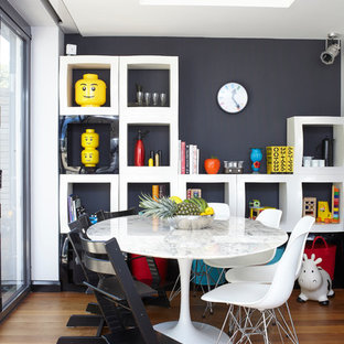 Design ideas for an eclectic dining room in London with black walls and medium hardwood flooring.