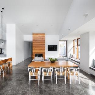 Foto di una sala da pranzo aperta verso il soggiorno design di medie dimensioni con pareti bianche, pavimento in cemento, pavimento grigio, camino classico e cornice del camino in legno