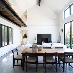 Imagen de comedor abovedado, actual, abierto, con paredes blancas, suelo de cemento, chimenea tradicional y suelo gris