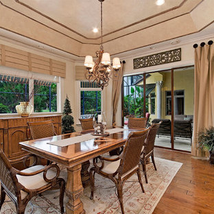 Example of a tuscan medium tone wood floor dining room design in Miami with beige walls and no fireplace