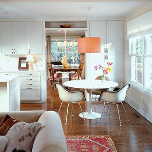Imagen de comedor de estilo americano, abierto, con paredes blancas y suelo de madera oscura