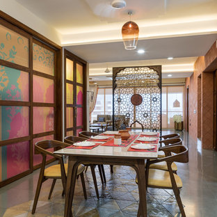 Immagine di una sala da pranzo etnica con pareti bianche e pavimento grigio