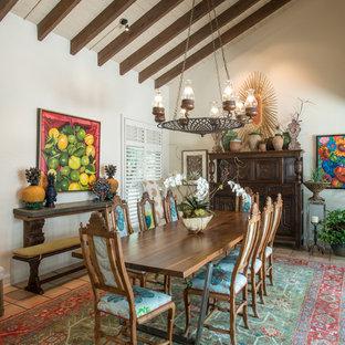 Cette image montre une grande salle à manger ouverte sur la cuisine bohème avec un mur beige, un sol en carreau de terre cuite et un sol orange.