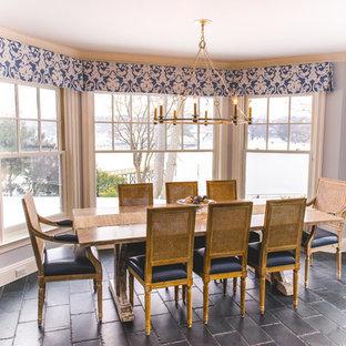 Modelo de comedor de cocina campestre, de tamaño medio, sin chimenea, con paredes azules, suelo de baldosas de cerámica y suelo negro