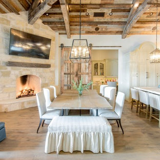 Expansive country kitchen/dining combo in Austin with white walls, light hardwood floors, a corner fireplace and a stone fireplace surround.