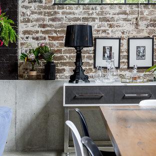 Idee per un'ampia sala da pranzo aperta verso il soggiorno industriale con pavimento in cemento, stufa a legna, cornice del camino in cemento e pavimento grigio