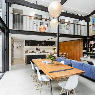 Ispirazione per un'ampia sala da pranzo aperta verso il soggiorno industriale con pavimento in cemento