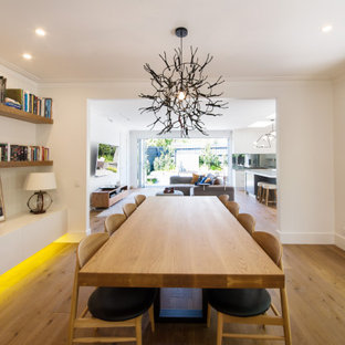 Expansive beach style open plan dining in Melbourne with white walls, medium hardwood floors and brown floor.