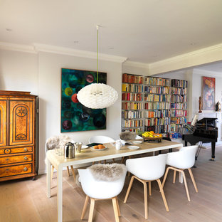 Inspiration for an eclectic dining room in London with grey walls and light hardwood flooring.