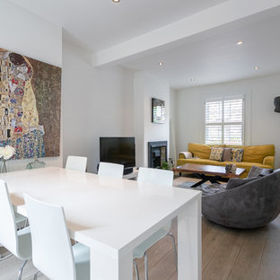 Photo of a small modern open plan dining room in London with white walls, light hardwood flooring, a metal fireplace surround and brown floors.