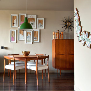 This is an example of a small retro dining room in Melbourne with beige walls and dark hardwood flooring.
