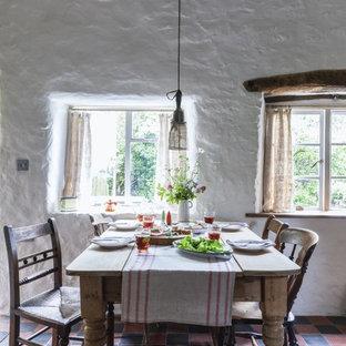 Идея дизайна: столовая в стиле кантри с белыми стенами, полом из терракотовой плитки и разноцветным полом