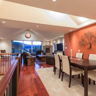 Immagine di una grande sala da pranzo aperta verso il soggiorno contemporanea con pavimento in legno massello medio e pareti arancioni