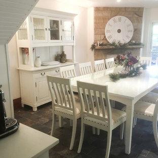 シドニーの中サイズのカントリー風おしゃれなダイニングキッチン (白い壁、スレートの床、コーナー設置型暖炉、石材の暖炉まわり、マルチカラーの床) の写真
