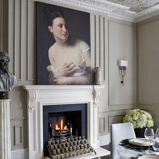 Example of a classic dark wood floor dining room design in London with a standard fireplace and beige walls