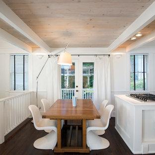 Foto di una sala da pranzo aperta verso la cucina bohémian con pareti bianche e parquet scuro