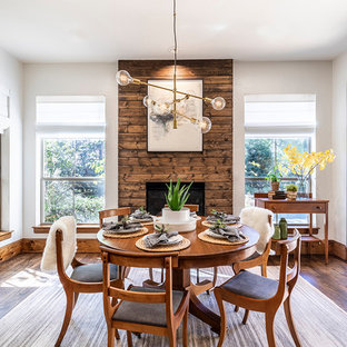 Inspiration for a scandinavian dark wood floor and brown floor dining room remodel in Dallas with white walls, a standard fireplace and a wood fireplace surround