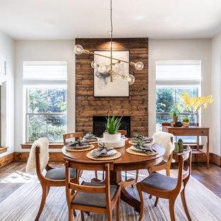 На фото: столовая в скандинавском стиле с белыми стенами, темным паркетным полом, стандартным камином, фасадом камина из дерева и коричневым полом с