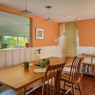 На фото: маленькая кухня-столовая в классическом стиле с оранжевыми стенами, пробковым полом и коричневым полом без камина с