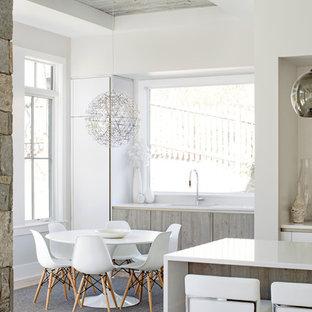 Modelo de comedor de cocina contemporáneo, pequeño, con paredes blancas, suelo laminado, marco de chimenea de hormigón y suelo beige