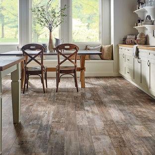 Esempio di una piccola sala da pranzo aperta verso la cucina tradizionale con pareti bianche, pavimento in vinile, nessun camino e pavimento marrone